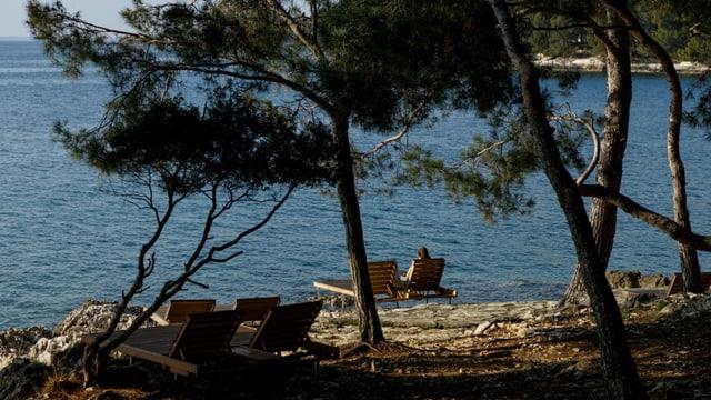 Strand mit Pinien. Liegestühle. In einem sitzt ein Mädchen.