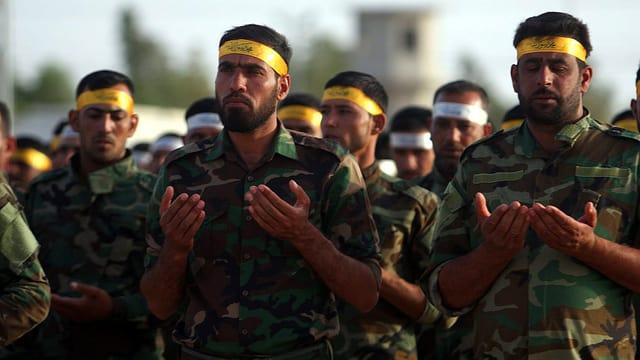 Schiitische Milizionäre halten im Gebet ihre Hände wie ein offenes Buch.