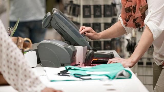 Eine junge Frau tippt etwas in eine elektronische Kasse in einem Kleiderladen ein.
