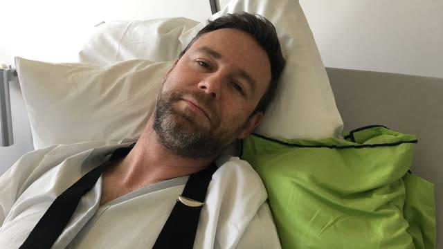 Moderator Nik Hartmann liegt in einem Krankenhausbett.