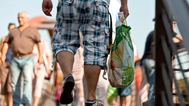 Konstanz: Ein Mann fotografiert von hinten mit einer vollen Einkaufstasche eines deutschen Deailhändlers.