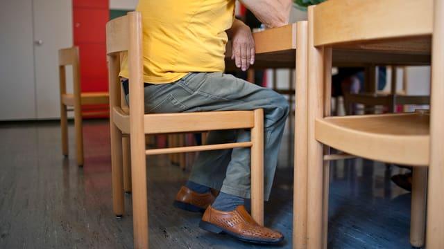 Älterer Herr sitzt in einer psychiatrischen Klinik an einem Tisch.