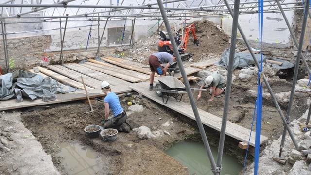 Drei Leute arbeiten in einer Ausgrabungsstätte. Knien auf dem Boden und buddeln mit den Händen in der Erde.
