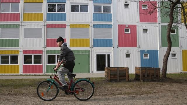 Ein Junge von Afghanistan fährt mit seinem Fahrrad durch eine Flüchtlingssiedlung in Berlin.