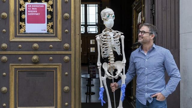 Mann mit Skelett. Das Skelett trägt Mundschutzmaske und Plastikhandschuhe.