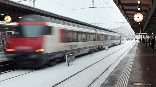 Ein Interregio-Zug flitzt durch einen Bahnhof, es hat Schnee auf den Geleisen.