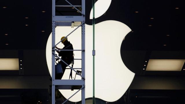 Ein Bauarbeiter auf einem Kran vor einem grossen Apple-Signet.