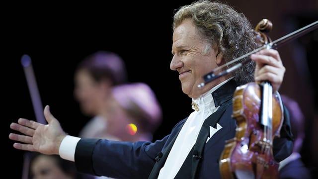 Ein Violinist mit ausgebreiteten Armen auf einer Konzertbühne.