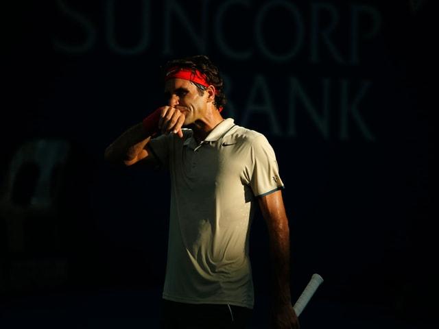 Roger Federer wischt sich das Kinn mit dem Handrücken ab.