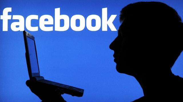 Der Schattenriss eines Mannes vor dem Facebook-Logo.