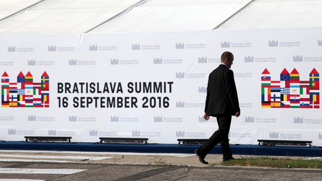 Ein Mann vor dem Hinweisschild auf das EU-Gipfeltreffen
