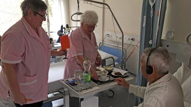 Zwei Frauen in rosa-weissen Schürzen servieren einem Spitalpatienten Kaffee.