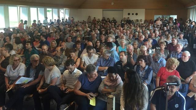 Viele Leute sitzen in einem vollen Saal.