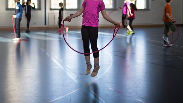 Ein Kind macht in einer Turnhalle Seilgumpen