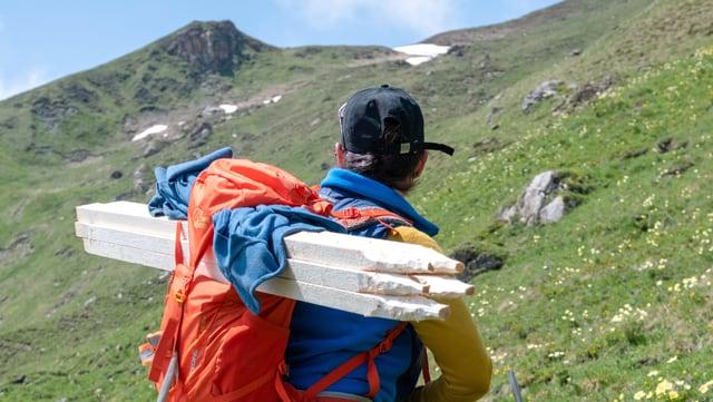 Eine Frau auf einer Alp, schwer bepackt mit Pfählen und Drahtrollen.