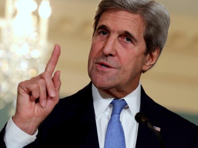 John Kerry spricht an einer Medienkonferenz und hält den Zeigefinger mahnend hoch.