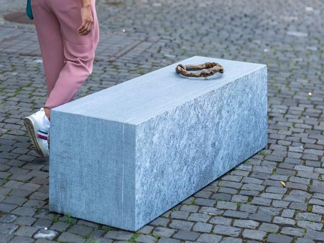 Eine Art Kette liegt auf einem rechteckigen Stein.