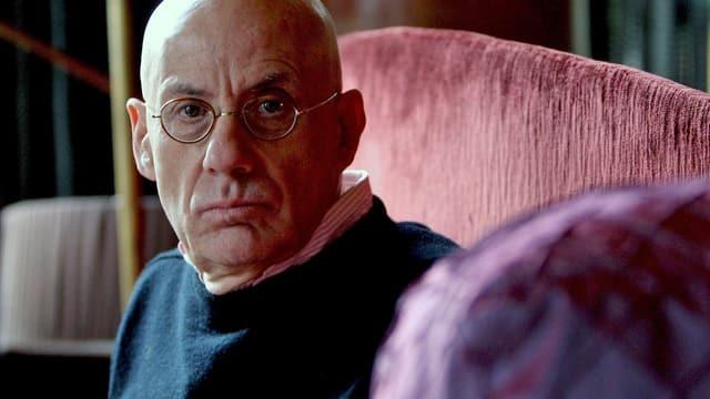Nahaufnahme des glatzköfpigen James Ellroy, der auf einem Sofa sitzt.
