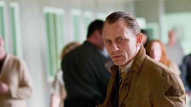Daniel Craig mit zurück gekämmten Haaren.