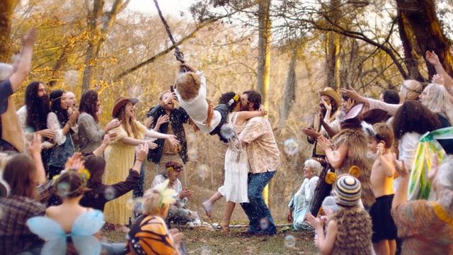 Heiratendes Hippie-Paar, umringt von einer applaudierenden Menschenmenge