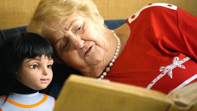 Alte Frau zeigt Roboter-Puppe Fotoalbum.