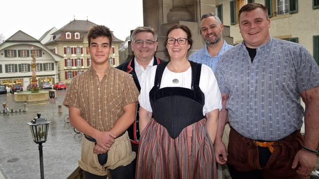Fünf Personen in Tracht und Schwingerhemd und Schwingerhosen vor einem mittelalterlichen Platz.