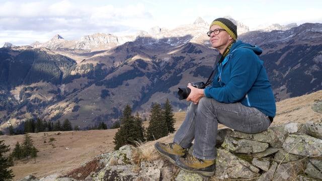 Ein Mann mit Brille und Kappe, welcher auf einem Stein auf einer Wiese sitzt.