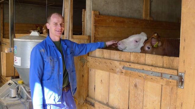 Mäster Beat Gloor in einem Stall mit zwei Kälbern.