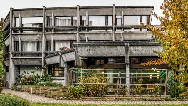 Eine Fassadenfront eines Altersheimes: Zweistöckies Gebäude mit grossen Fenster in weinroten Fensterrahmen. Das Gebäude selbst ist aus Beton, an welchem viele Witterungsspuren in Form von schwarzen Verfärbungen zu sehen ist.