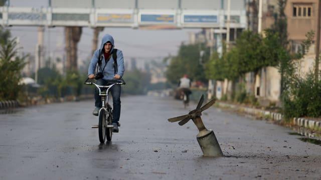 Fahrradfahrer neben einer Streubombe
