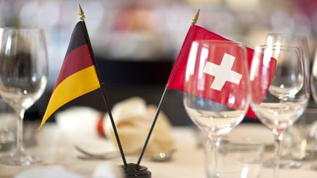 Eine deutsche und eine Schweizer Flagge stehen auf einem Tisch