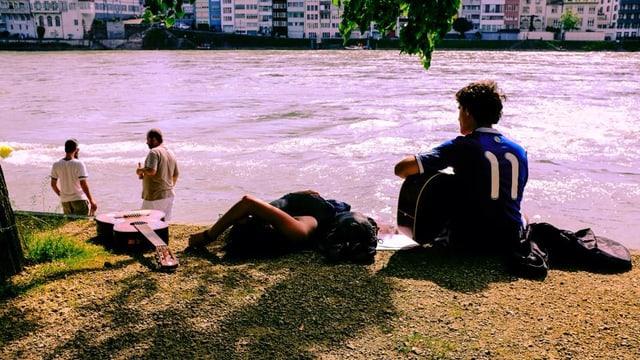 Menschen sitzen gemütlich am Fluss