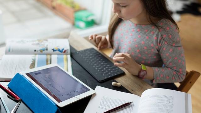 Ein Mädchen macht Hausaufgaben an einem Tablet.
