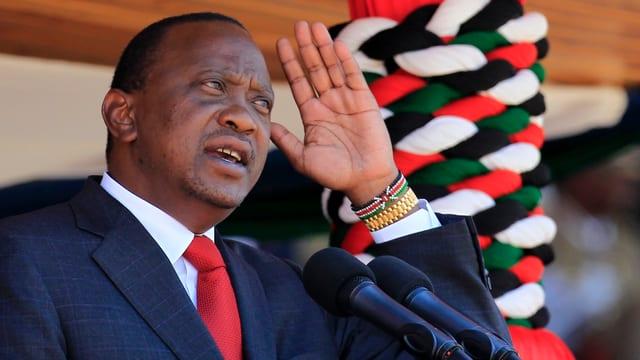 Kenyatta iin dunelblauem Anzug und roter Krawatte spricht in Mikrofone und gestikuliert.