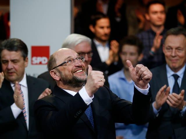 Martin Schulz schaut nach oben und hat beide Daumen ausgestreckt.