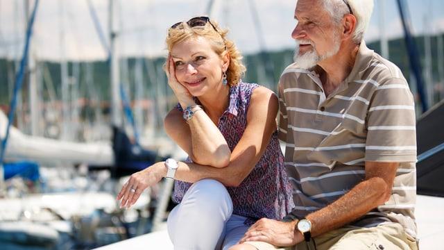 Ein älteres Ehepaar sitzt an einem Hafen und lächelt.