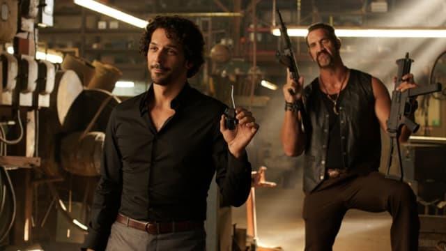 Zwei bewaffnete Typen stehen bewaffnet in einem Keller hintereinander.