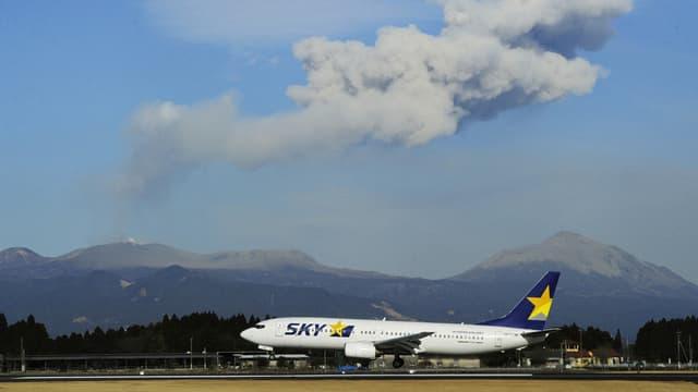 Ein Flugzeug auf einer Landebahn vor einem Vulkan, der Asche spuckt.
