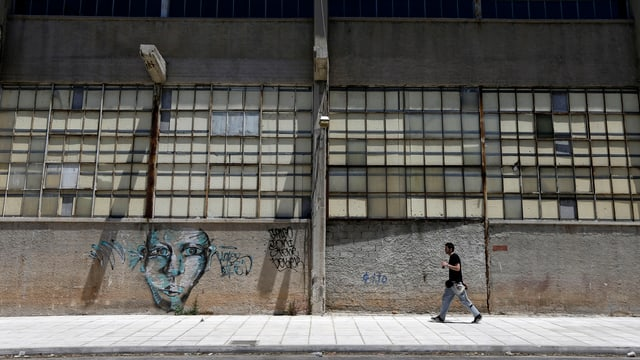 Ein Mann geht an einer geschlossenen, alten Fabrik vorbei.