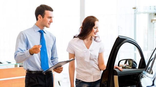Ein Verkäufer und eine Kundin betrachten ein Auto
