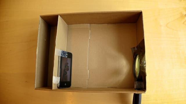 Die Schachtel von oben, Handy steht links, rechts die Lupe im Loch.