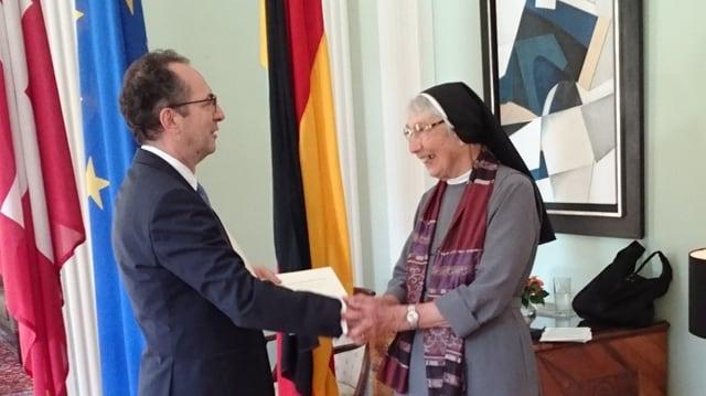 Eine Mann übergibt einer Nonne einen Orden.