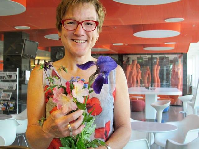 Porträt von Gärtnerin Silvia Meister mit Blumen in der Hand.