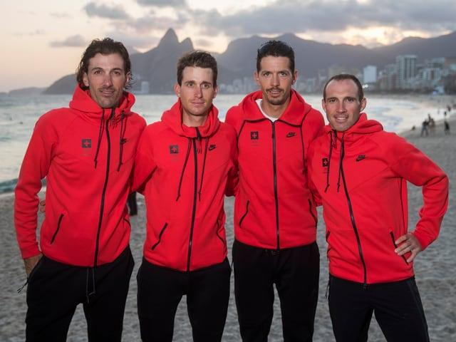 Vier Radfahrer posieren am Strand.