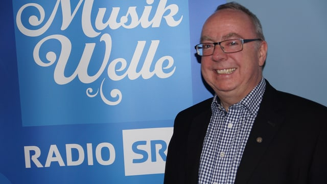 Mann vor SRF Musikwelle-Plakat.