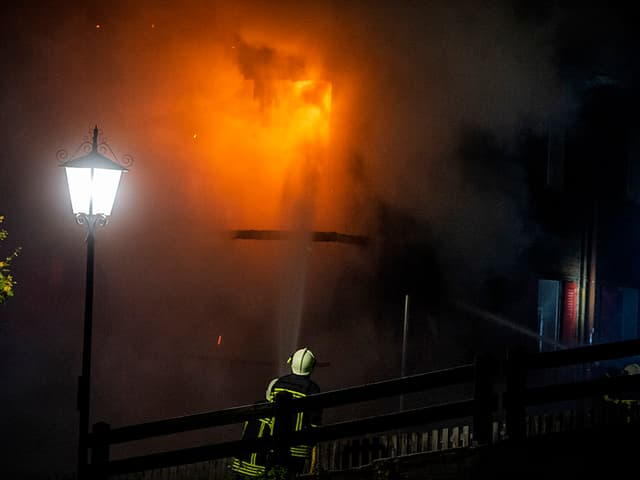 Ein Feuerwehrmann vor einer Brandstelle.