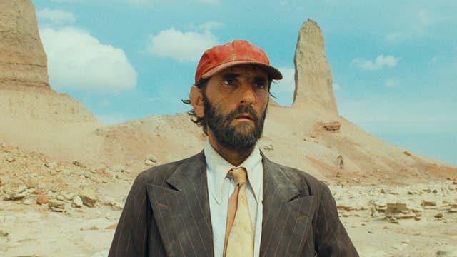 Mann mit roter Baseballmütze und Anzug in einer Wüstenlandschaft