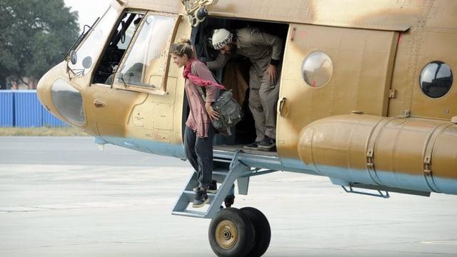 Eine Frau und ein Mann steigen aus einem Armeehelikopter aus.