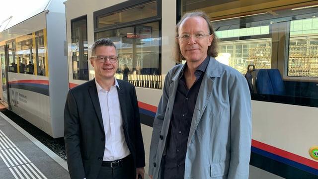 Zwei Männer stehen vor einem Zug.