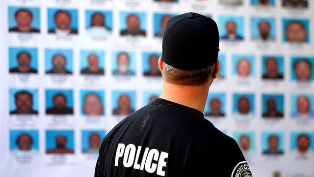 Englischer Polizist von hinten vor einer Tafel mit Dutzenden Fahndungsfotos.